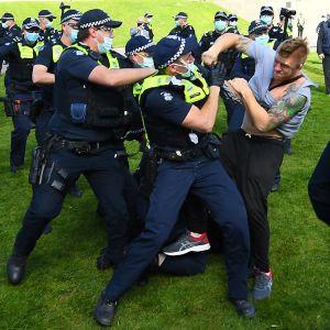 Mielenosoittaja ajautui käsirysyyn poliisien kanssa sotamuistomerkin edustalla Melbournessa Australiassa 5. syyskuuta 2020.