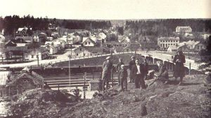 Bild från den gamla järnvägsbron 1941 i Karis. Människor sitter på berget framför bron.