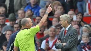 Mike Dean visar upp Arsene Wenger på läktaren under en annan Premier League-match.