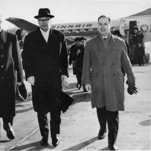 Kekkonen anländer till Tallinns flygplats den 11 mars 1964. På hans högra sida ordföranden i Estlands Högsta sovjets presidium Aleksei Müürisepp. TIll vänster om Kekkonen tolken Hillar Laane.