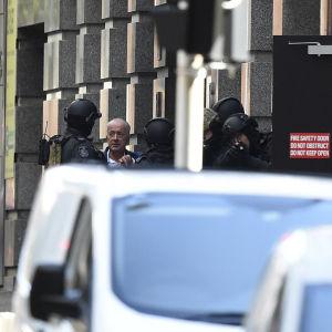 En en person som tidigare hållits gisslan talar med polisen på Phillip Street nära Lindt kaféet.