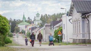Ihmisiä kävelemässä kadulla, reunoilla puutaloja, taustalla kirkko