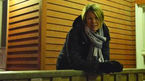 En kvinna i vinterkläder lutar sig över ett träräcke utanför en röd träbyggnad. Det är mörkt ute och bilden är lite dunkel.