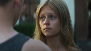 Anneli (Nelly Axelsson) i närbild när hon står och tittar på Wojtek som står med ryggen mot kameran.