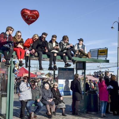 Juhlijoita odottamassa Mantan lakitusta raitiovaunupysäkin päällä