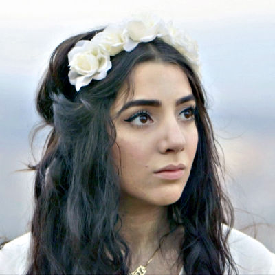 Programledare Gina Dirawi med blommor i håret.