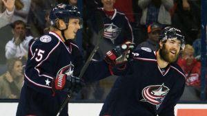 Två blåklädda ishockeyspelare firar mål i NHL.