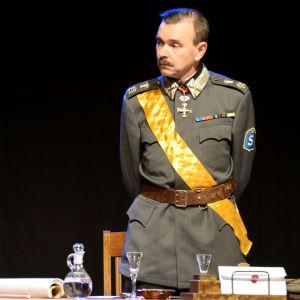 Scen ur teatern Mannerheim - mannen och myten. Mannerheim (Stefan Elf) står vid ett skrivbord. Till vänster syns skådespelaren Mats Enberg och till höger skådespelaren Kari Danielsson.