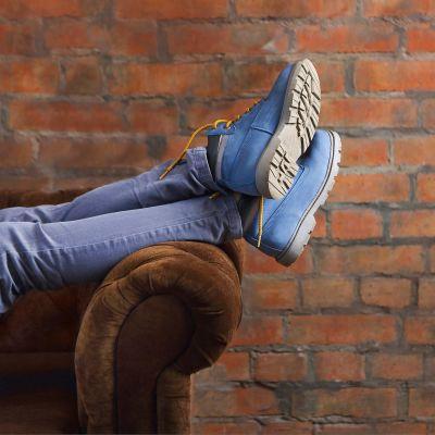 Nuori nainen makaa sohvalla, kengät jalassa.