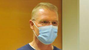 Man i glasögon och munskydd med passerkort från Vasa centralsjukhus runt nacken.