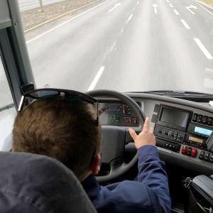 Busschaufför sitter i en buss och kör på en väg.