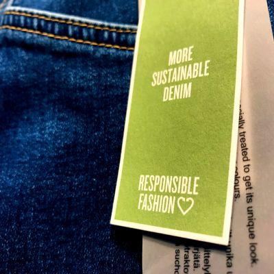 ett jeansplagg med en lapp som talar om att det är hållbart mode