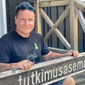 En man poserar sittandes på en trappa med händerna på en skylt där det står tutkimusasema.