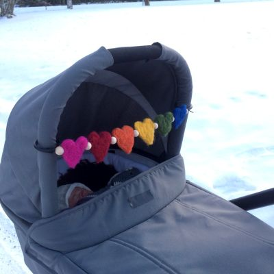 Barnvagn med en tovad mobil med hjärtan i regnbågens färger