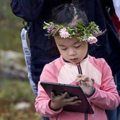 Kiinalainen tyttö katsoo tablettia.