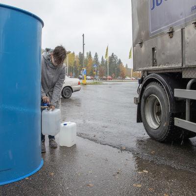 Kerttu Karppinen laskee vettä kanisteriin juomavesisäiliöstä.