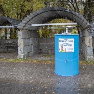 Iso sininen puhdasta juomavettä - tarralla varustettu astia Petäjävedellä kadulla.