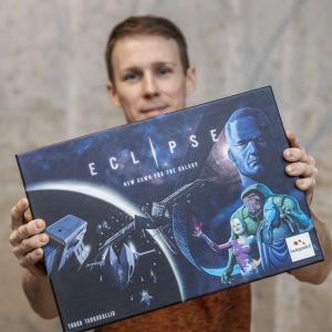 Juuso Marttila Eclipse-lautapeli laatikko kädessään.