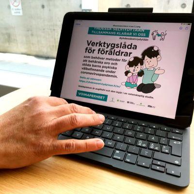 en hand vid en surfplatta som visar en bild på en hemsida