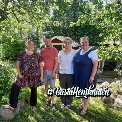 Fyra personer som står i en trädgård.