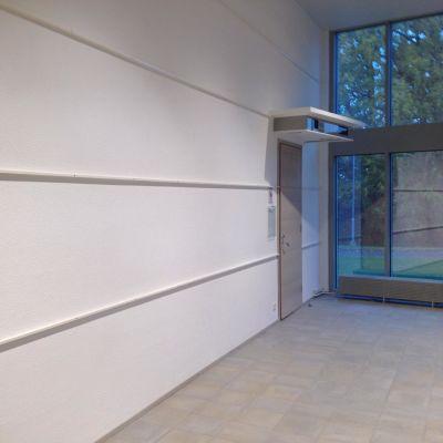 En dörr och en vit vägg. Inomhus.