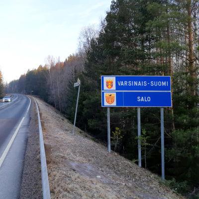 En skylt där det står Egentliga Finland och en annan där det står Salo vid en väg. På vägen kör en bil.