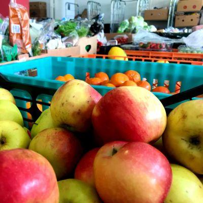 en hög med äpplen och en korg med mandariner och andra livsmedel i bakgrunden