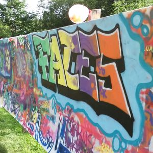En grafittivägg där det står Faces med färggranna bokstäver.