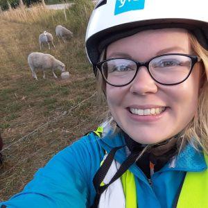 En selfie av Malin Valtonen iklädd cykelhjärm. I bakgrunden syns får i en hage.