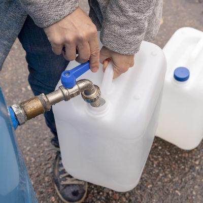 Ihminen pitelee vesikanisteria ja laskee vettä isommasta säiliöstä kanisteriin.