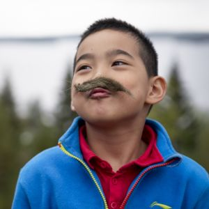 Kiinalainen poika naavaviikset huulissa.