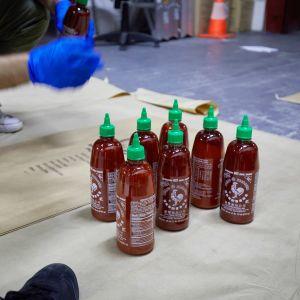 Sju flaskor srirachasås som står på golvet i smugglarhärva i Australien.