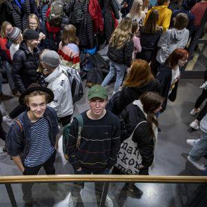 Pojat seisovat keskellä oppilasröykkiötä