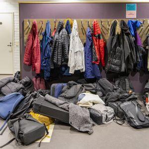 Paljon koululaisten vaatteita ja reppuja naulakossa.