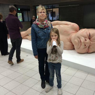 Nainen ja pikkutyttö vastasyntynyttä esittävän teoksen edessä Sara Hildénin taidemuseossa.