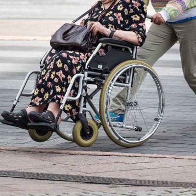 Nainen työntää vanhusta rullastuolissa.
