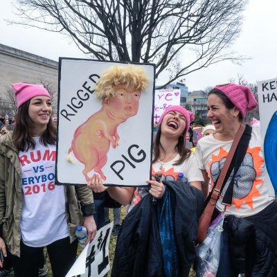 """Kolme naista mirrihatuissa pitävät Trumpia pilkkaavia kylttejä: """"Rigger pig"""" ja """"Keep your tiny hands off our rights."""""""