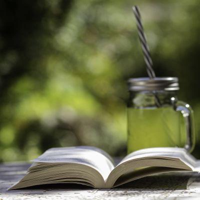 Avonainen kirja ulkopöydällä ja limonadilasi.