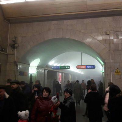 Kuvassa ihmisiä purkautumassa ulos metrosta 3. huhtikuuta Pietarissa. Metroaseman käytävillä leijuu pientä savua.