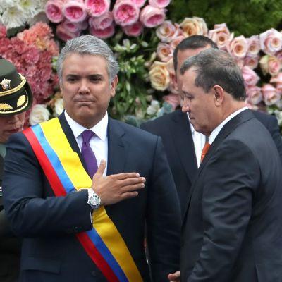 Kuvassa värikäs nauha kiinnitetään presidentin ympärille.