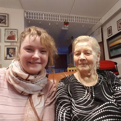 Nainen selfiessä vieressä istuvan eläkeläismummon kanssa.