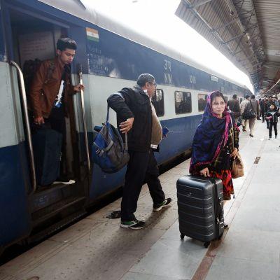 Matkustajia Delhin rautatieasemalla.