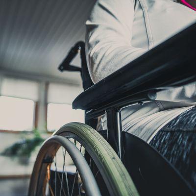 Lähikuva pyörätuolissa istuvan, valkoiseen huppariin ja uhreilutrikoisiin pukeutuneen ihmisen kädestä ja pyörtuolin käsinojasta.
