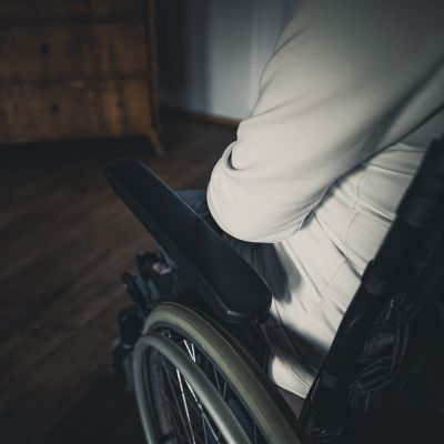 Valkoiseen huppariin pukeutunut ihminen istuu pyörätuolissa, lähikuva ylhäältäpäin henkilön olkapäästä ja pyörätuolin käsinojasta.