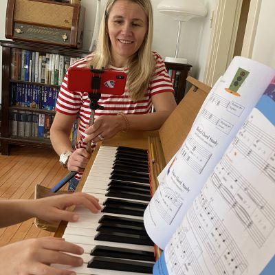 Nainen kuvaa kännykällä kun lapsi soittaa pianoa.