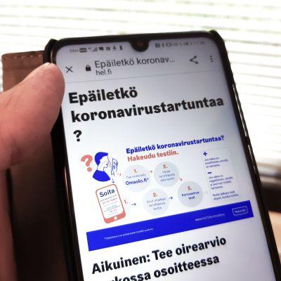 Kännykässä näkyvillä Helsingin kaupungin koronaneuvontasivut.