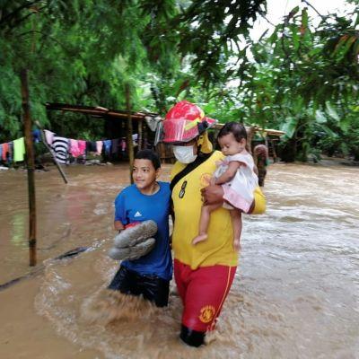 Pelastustyöntekijä kantaa pikkulasta tulvavedessä