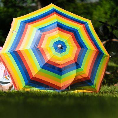 Sateenkaaren värinen päivänvarjo nurmikolla.