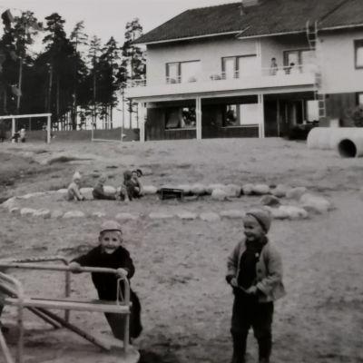 Lapset leikkivät Kärpäsen lastentalon pihalla karusellissa ja hiekkalaatikolla 1950-luvulla