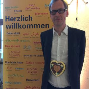 Kaj Arnö vid en tysk skylt som hälsar honom hjärtligt välkommen i landet.